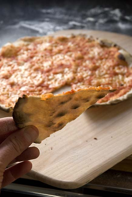 Cracker-crust-pizza-is-so-thin-the-light-shines-through-it